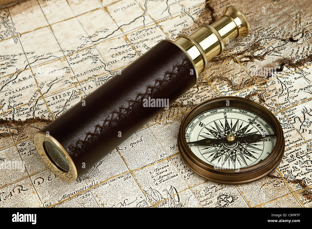Vintage brass telescope and compass over antique map - Stock Image