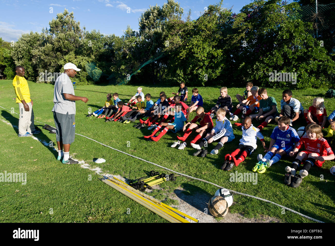 Football coaches addressing junior players during training Cape Town South Africa - Stock Image