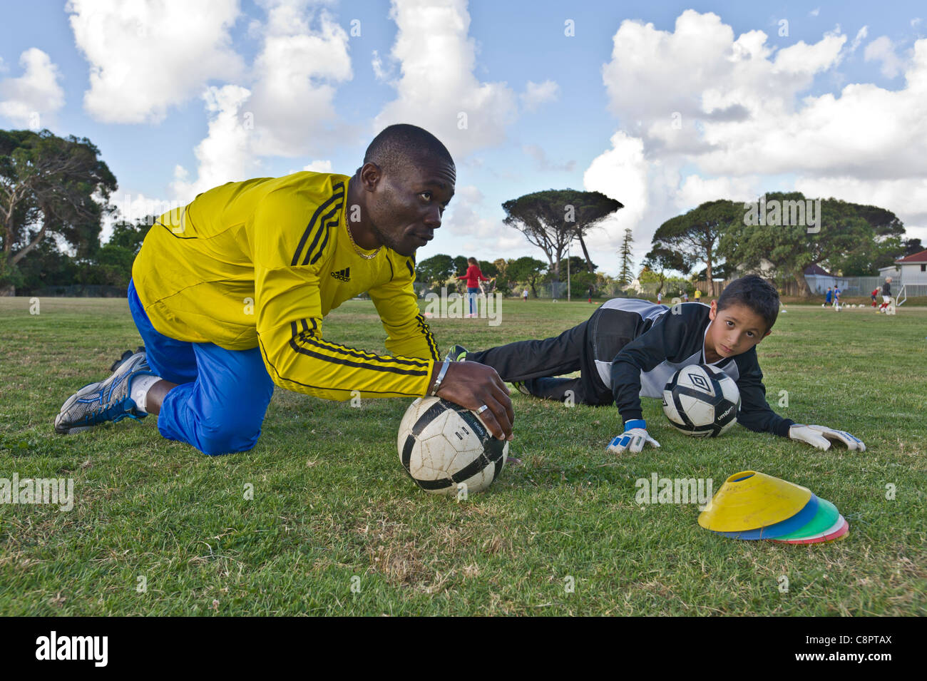 Goal keeper coach instructs junior player Cape Town South Africa - Stock Image