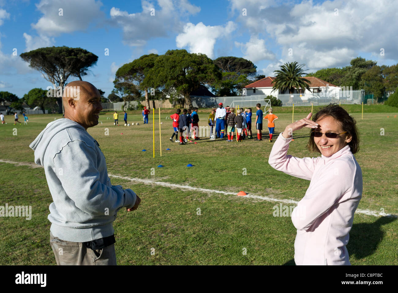 Parents watching junior football players practicing ball skills Cape Town South Africa - Stock Image