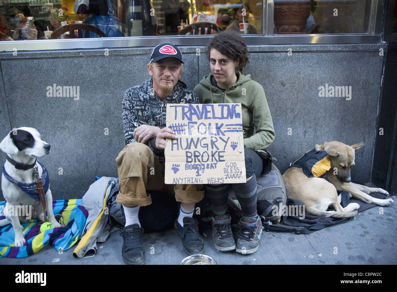 As their sign says traveling couple on the road, hungry and broke. Broadway, downtown Manhattan, NYC. - Stock Image