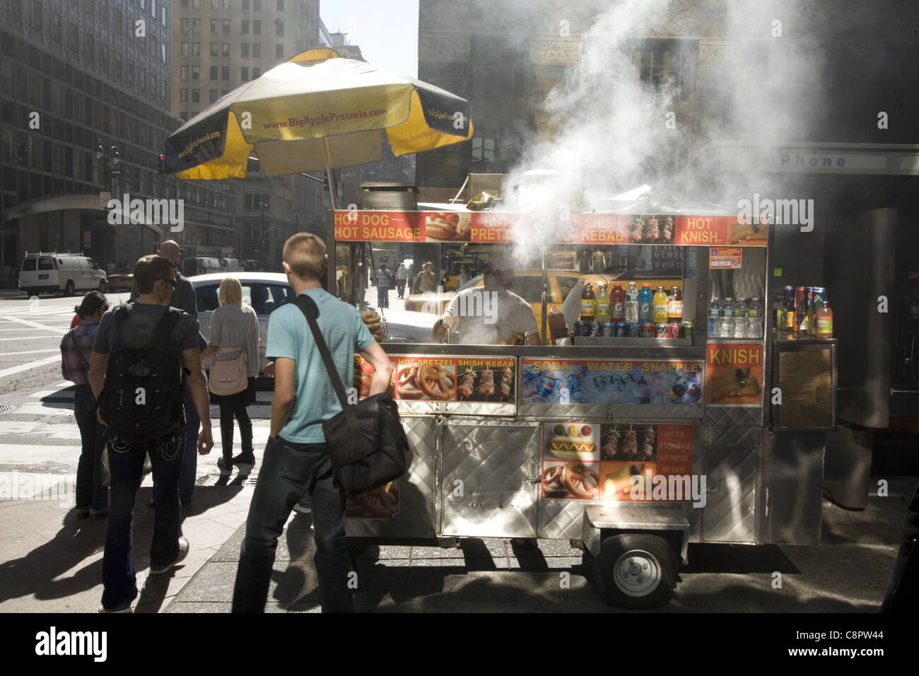Food vendor cooks on the street in midtown Manhattan and pollutes the environment around him. - Stock Image