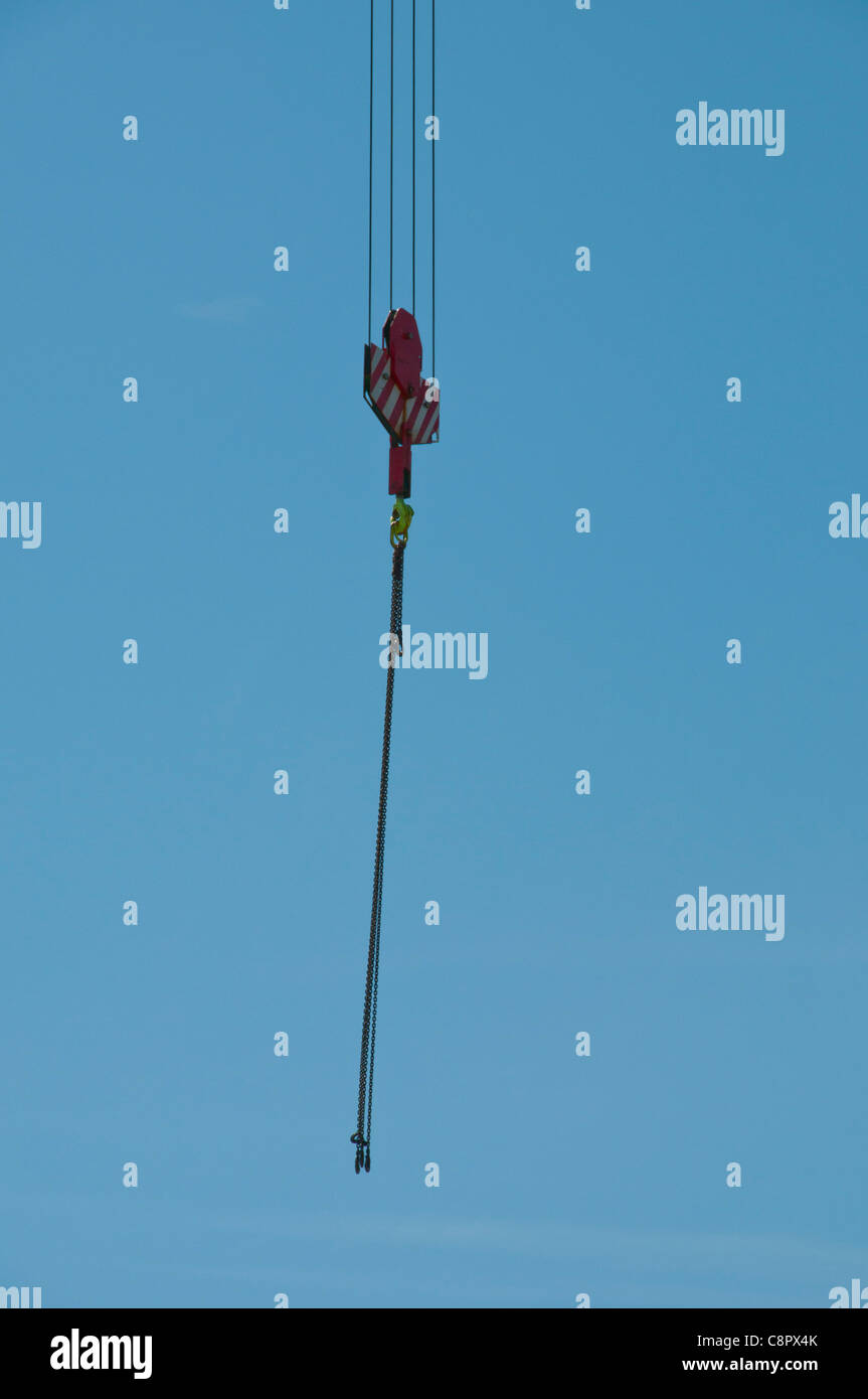 single crane hook and chain in cloudless blue sky blowing in wind - Stock Image