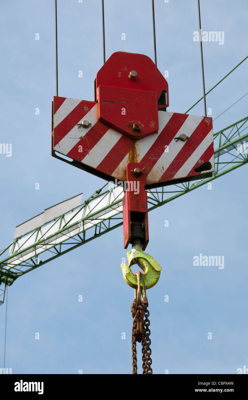 close up of hook on crane with crane arm in background - Stock Image