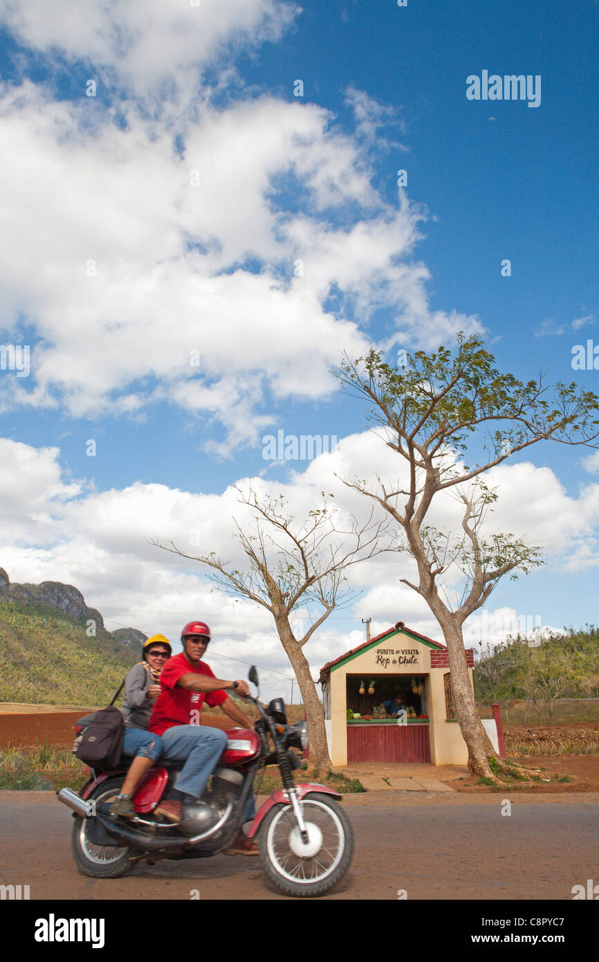 PINAR DEL RIO: COUPLE ON MOTORBIKE AND A ROADSIDE FRUIT SHOP IN THE VINALES VALLEY - Stock Image