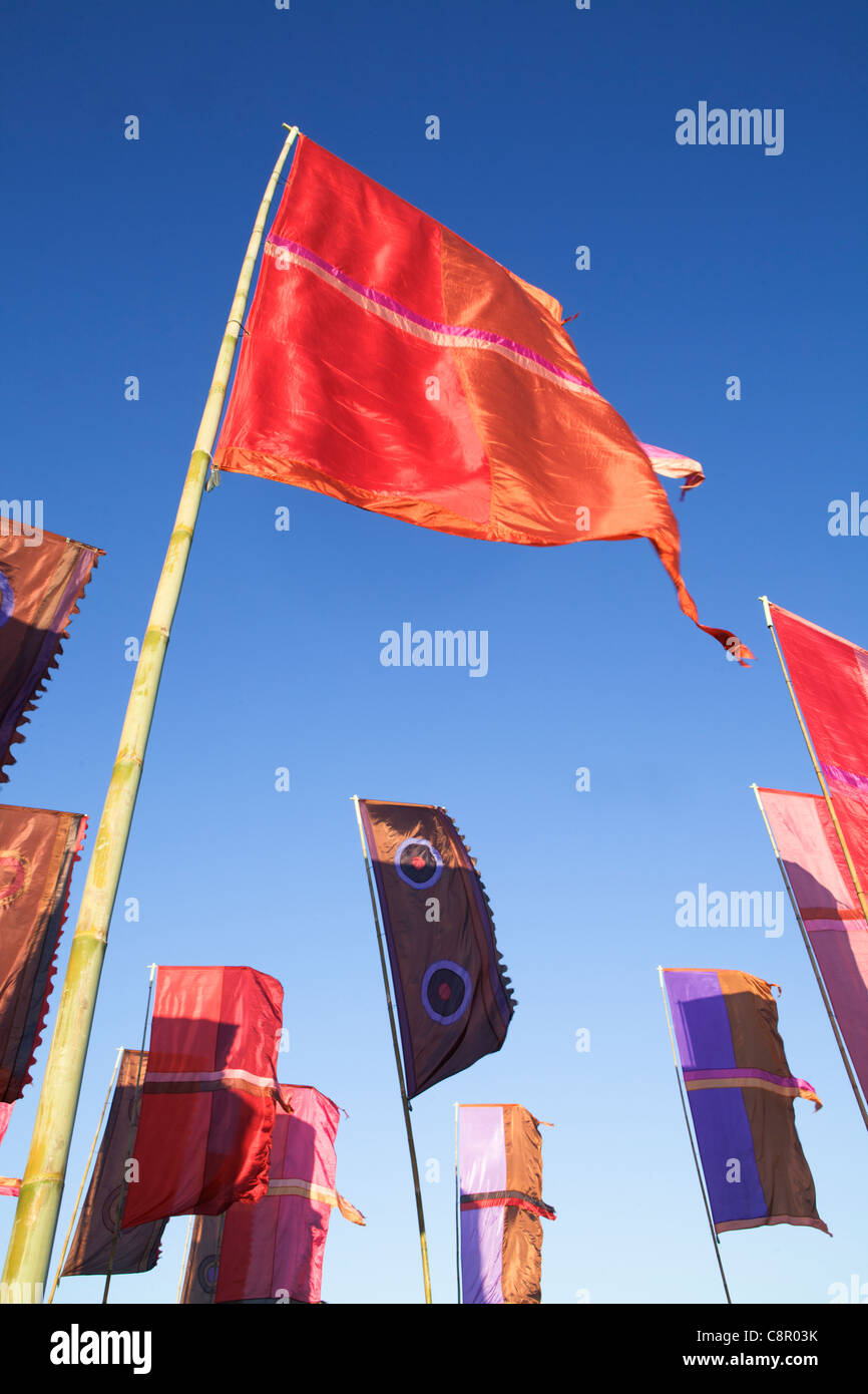 Colourful flags flying in the wind against a blue sky - Stock Image