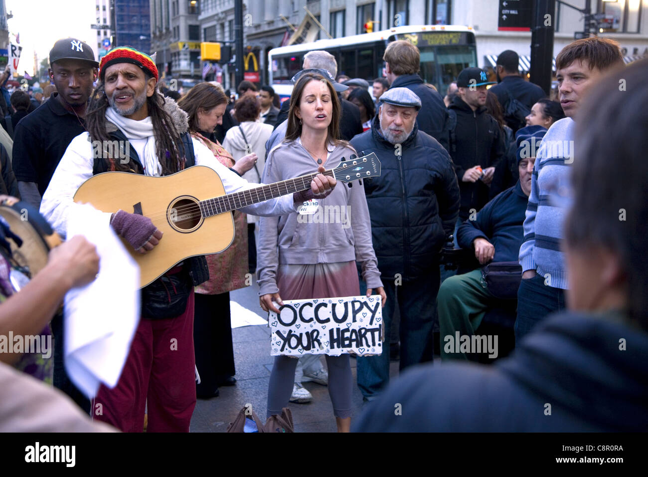 Group sings at Occupy Wall St. at Liberty Square in NYC. - Stock Image