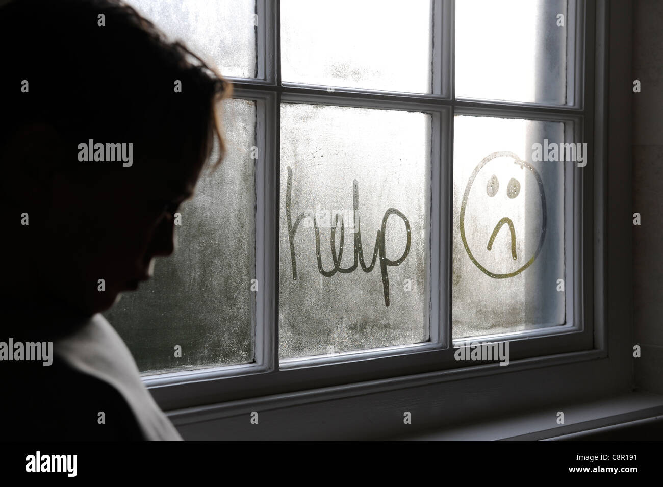 6 year old child writing help on a window in condensation - Stock Image