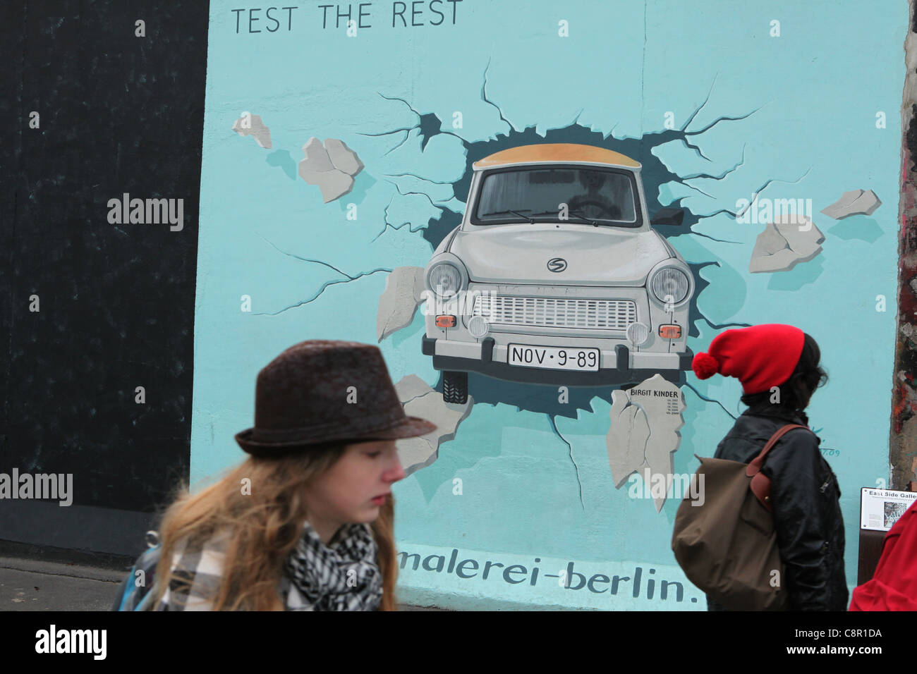 Trabant breaking through the wall pictured on the Berlin Wall in East Side Gallery in Berlin, Germany. - Stock Image