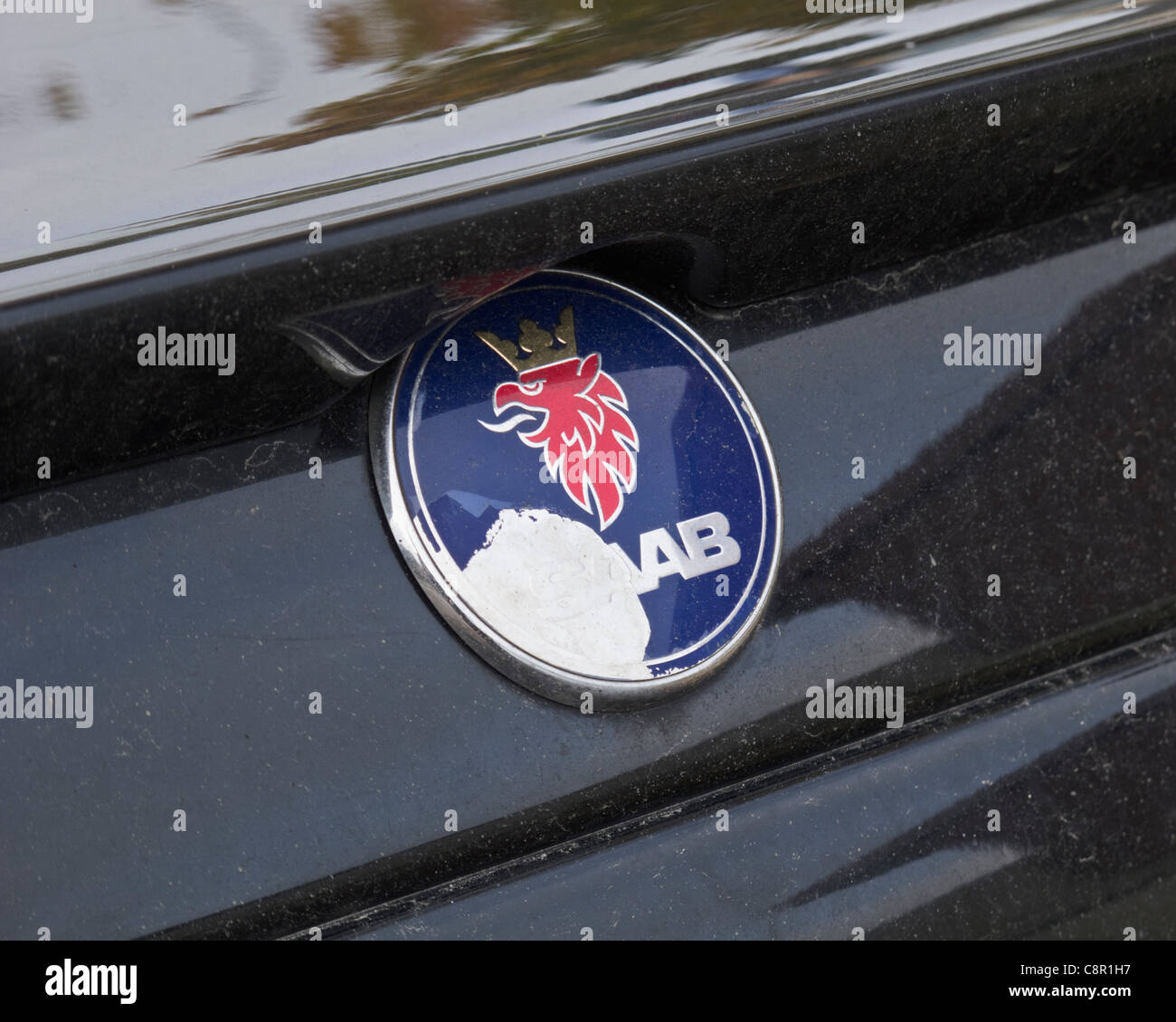 Close-up of damaged SAAB car logo on a black car. FOR EDITORIAL USE ONLY. - Stock Image