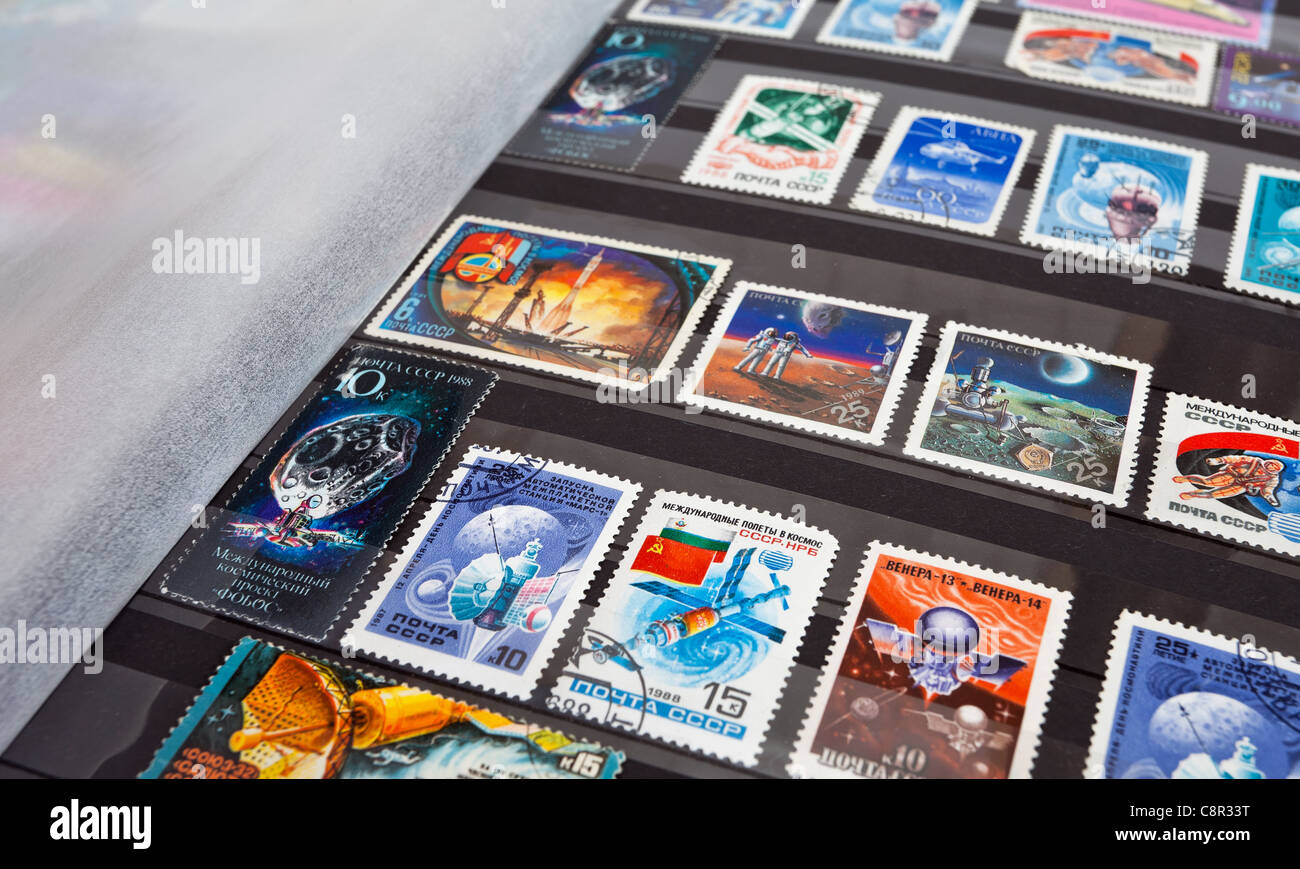 Postage stamps in album. A few in focus the rest unfocussed - Stock Image