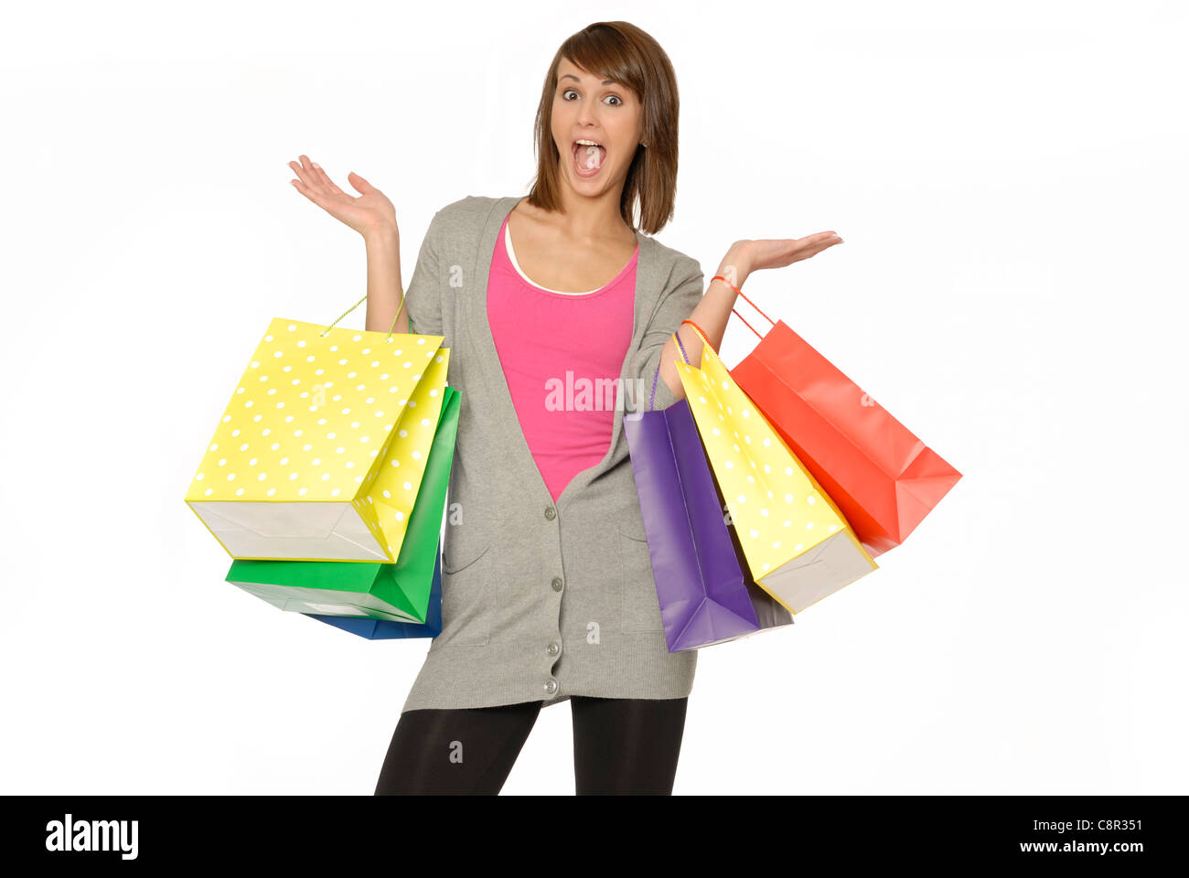 Pretty Young Woman With Excited Expression, Holding Many Bright Colored Shopping Bags - Stock Image