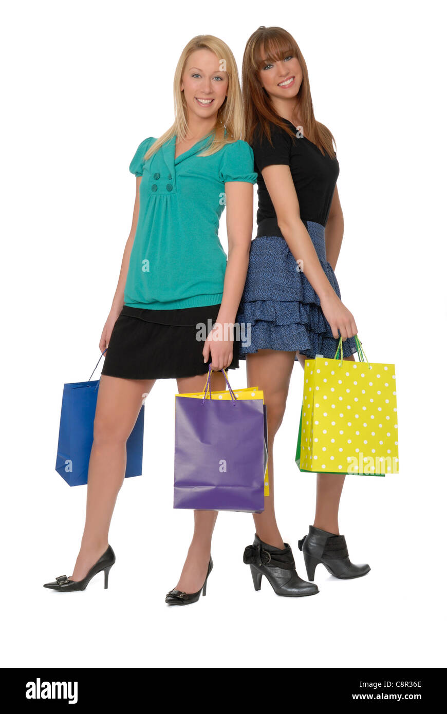 Two woman friends in their early 20s, holding shopping bags, smiling and looking at viewer. - Stock Image