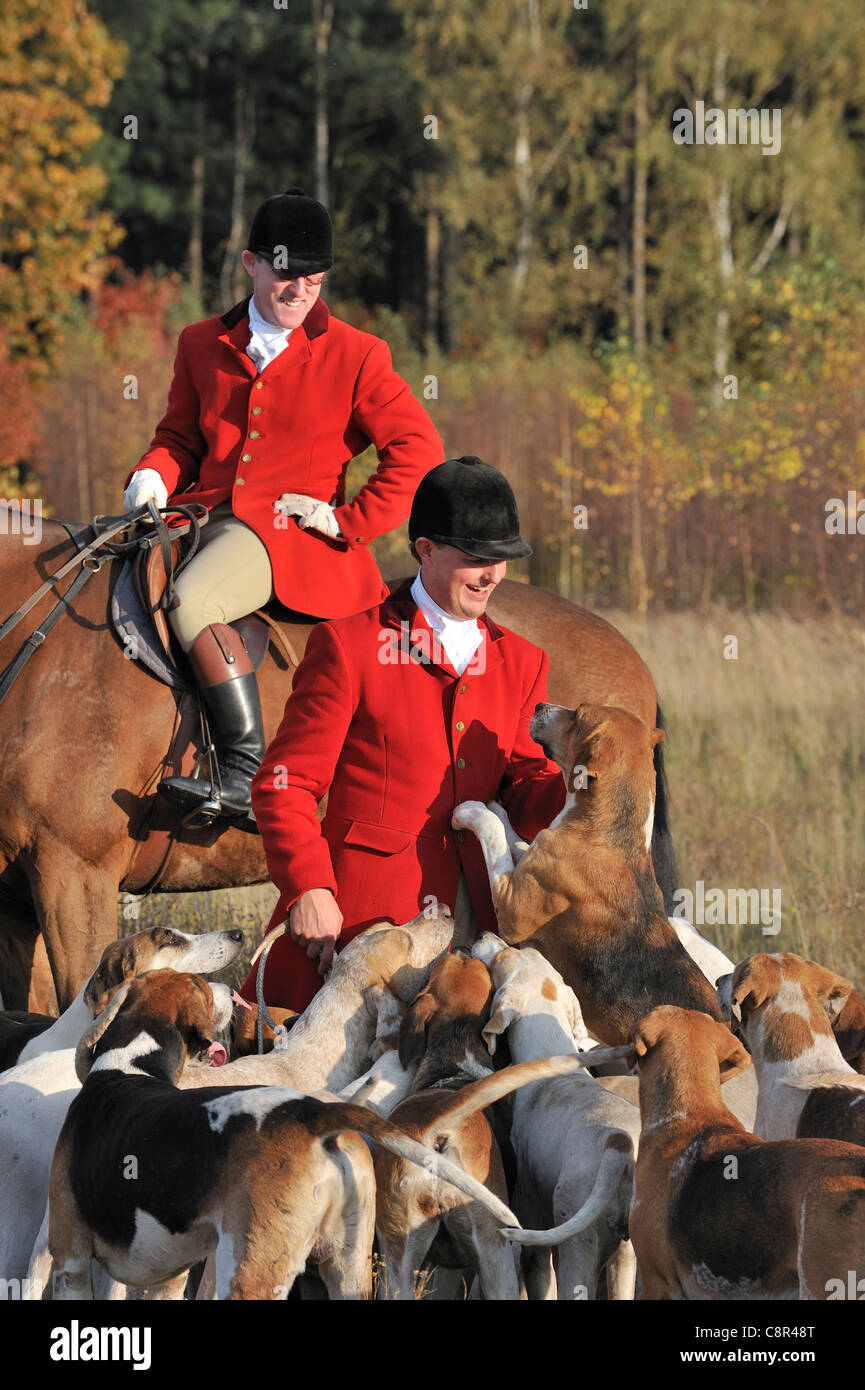 Hunters wearing red coats on horseback with pack of hounds during drag hunting in autumn, Europe - Stock Image