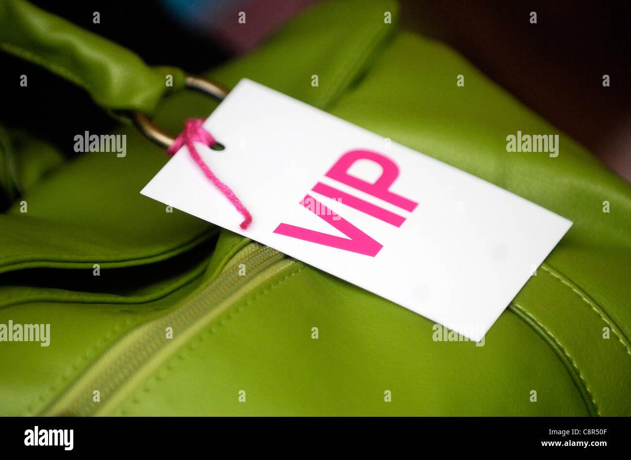 VIP pass on a woman's handbag at an event. - Stock Image