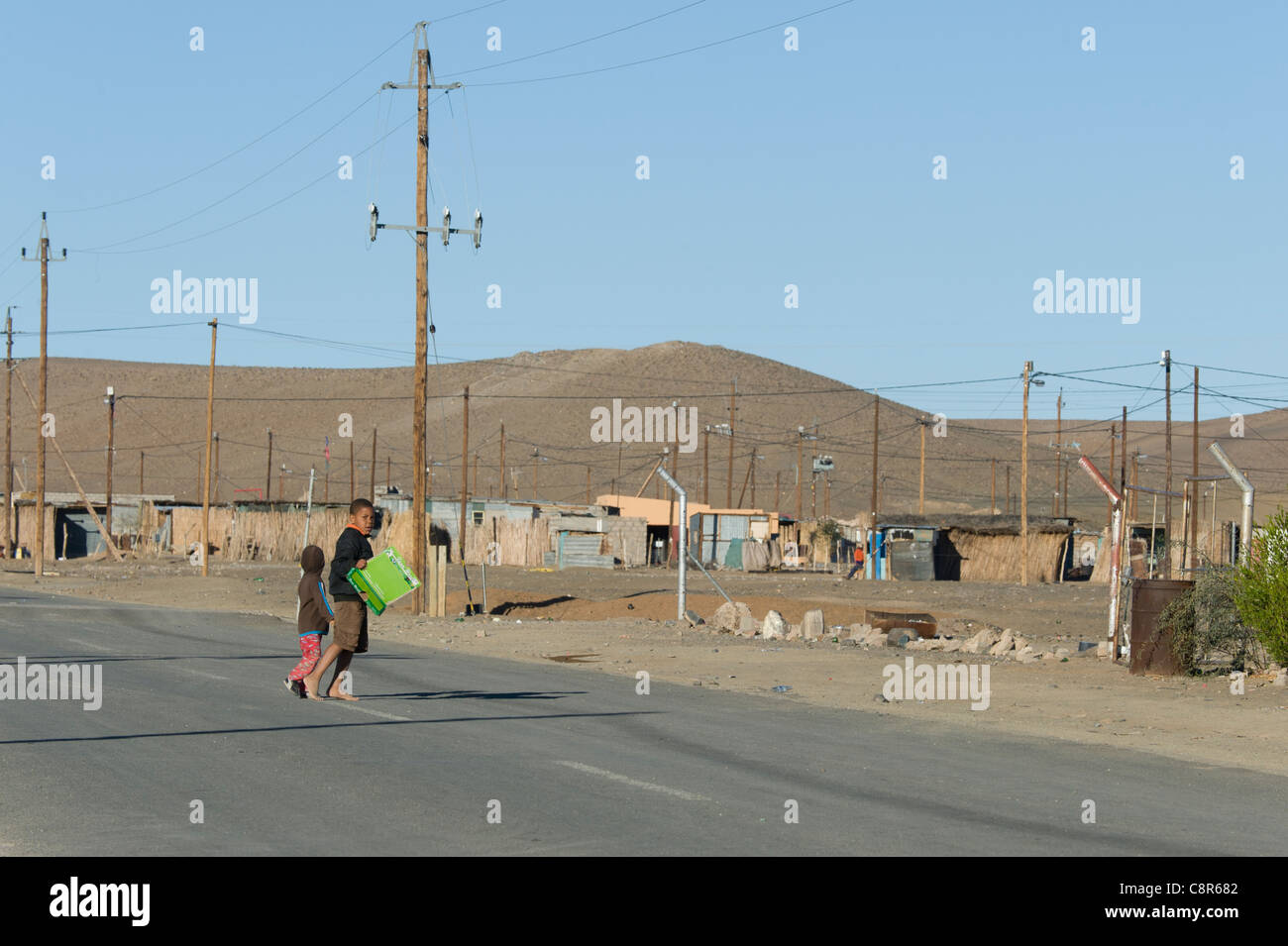 Children crossing a road in Noordoewer Namibia - Stock Image