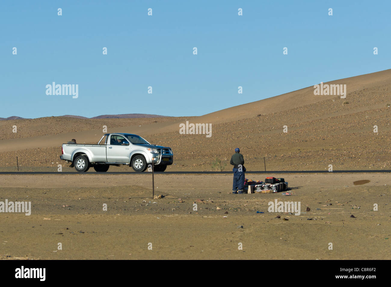 Man waiting with goods waiting for transport in Noordoewer Namibia Stock Photo