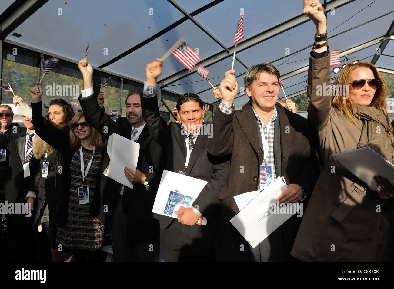 As they became U.S. citizens in a naturalization ceremony on Liberty Island, the 125 new citizens waved U.S. flags - Stock Image