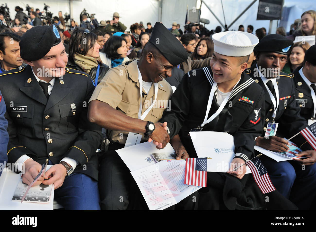 On Oct. 28, 2011, at a naturalization ceremony on Liberty Island, two of the new U.S. citizens congratulated each - Stock Image
