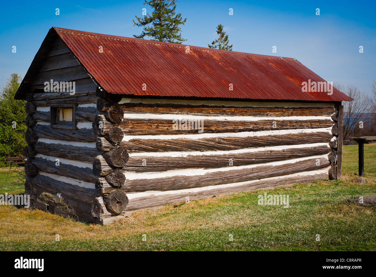 A very small but long old log cabin with rusted tin roof at Stock