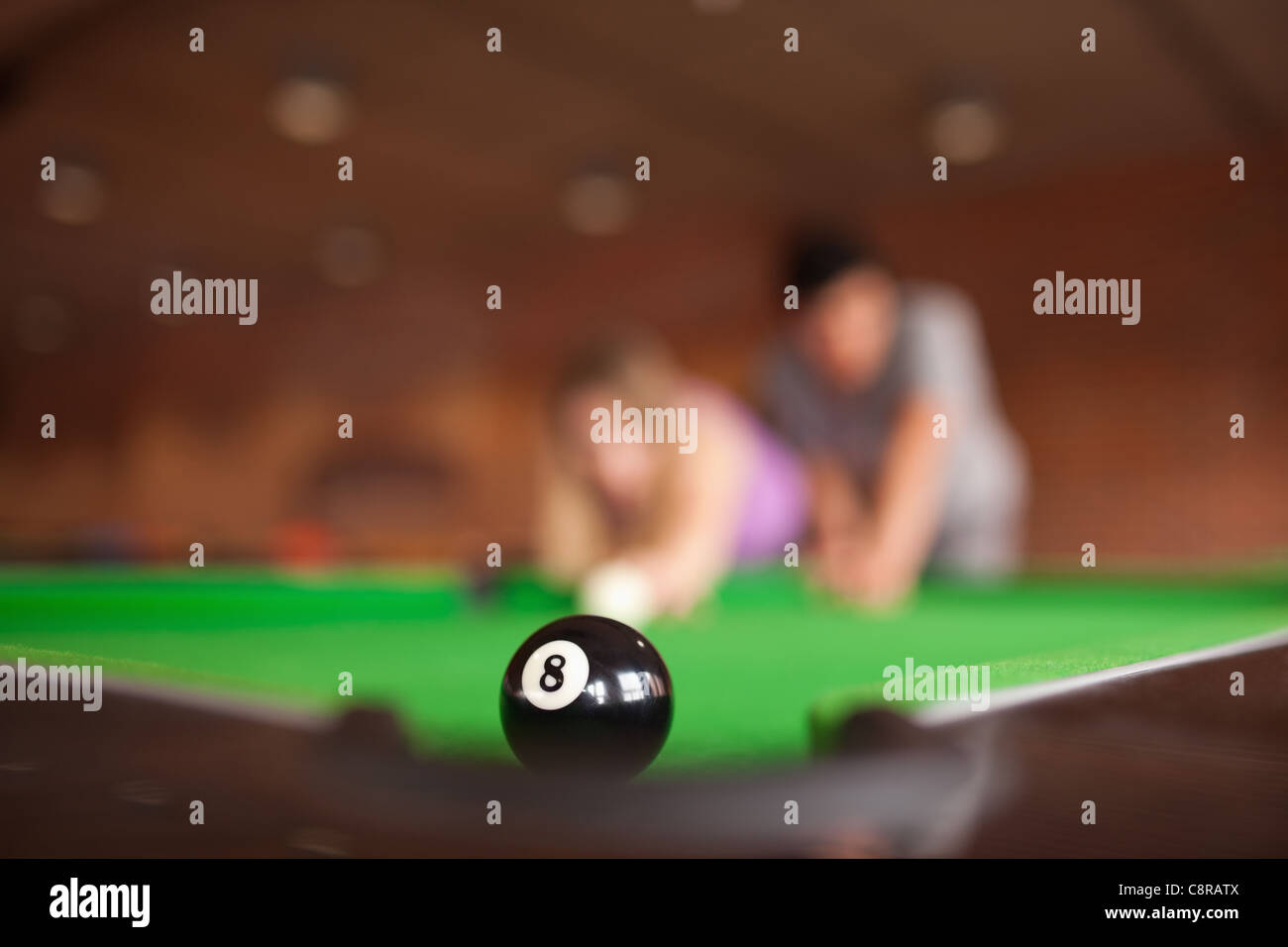 Man teaching pool to his fiance - Stock Image