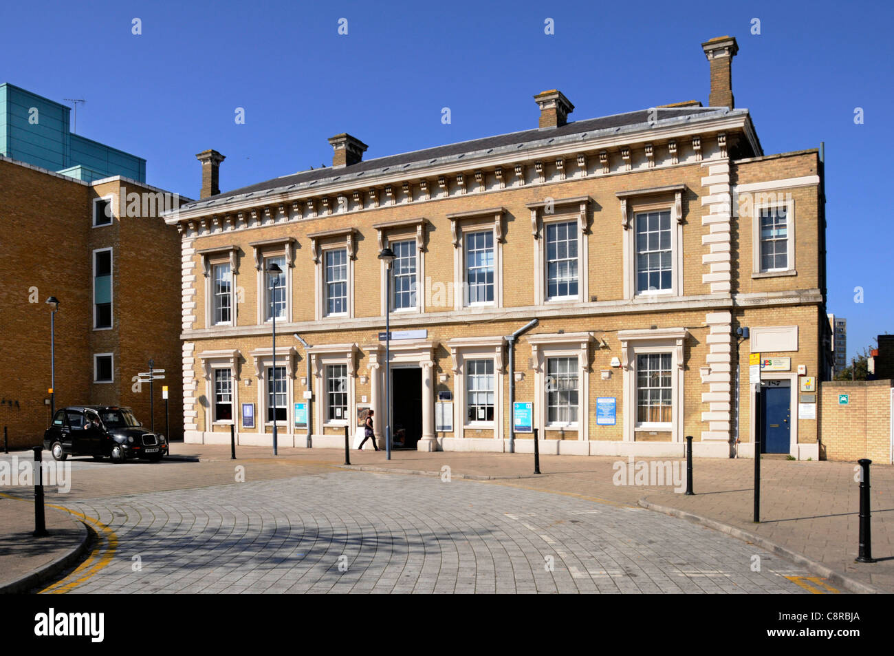 Brick front façade & entrance to Greenwich train station with access to Docklands Light Railway station black cab Stock Photo