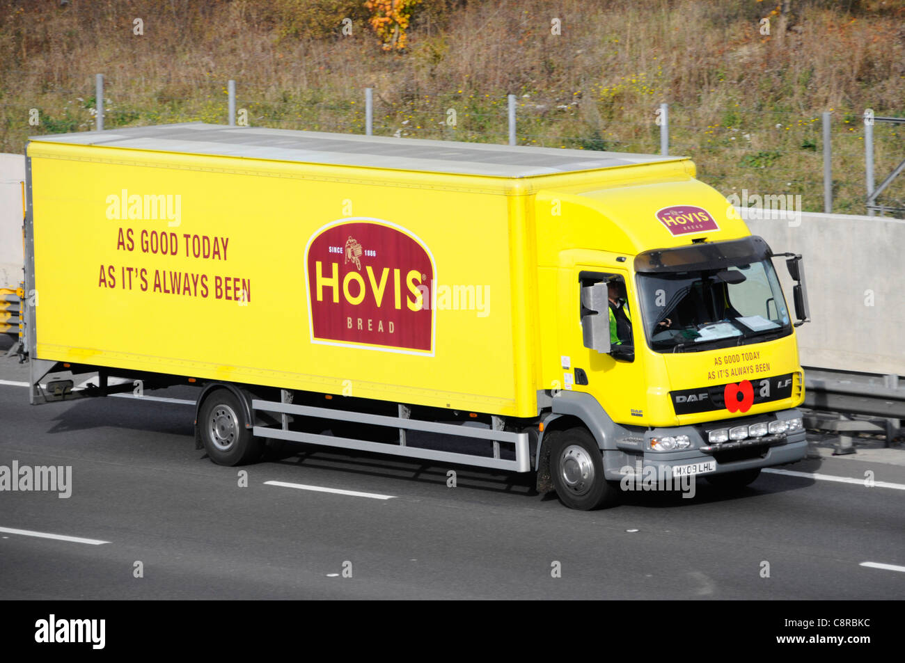 Hovis bread food supply chain rigid body delivery lorry yellow truck displaying logo and advertising driving along - Stock Image