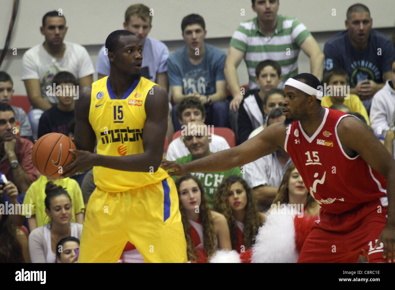 Maccabi Tel Aviv Basketball team (Yellow) Playing Hapoel Gilboa-Galil (Red) on October 16th 2011. - Stock Image