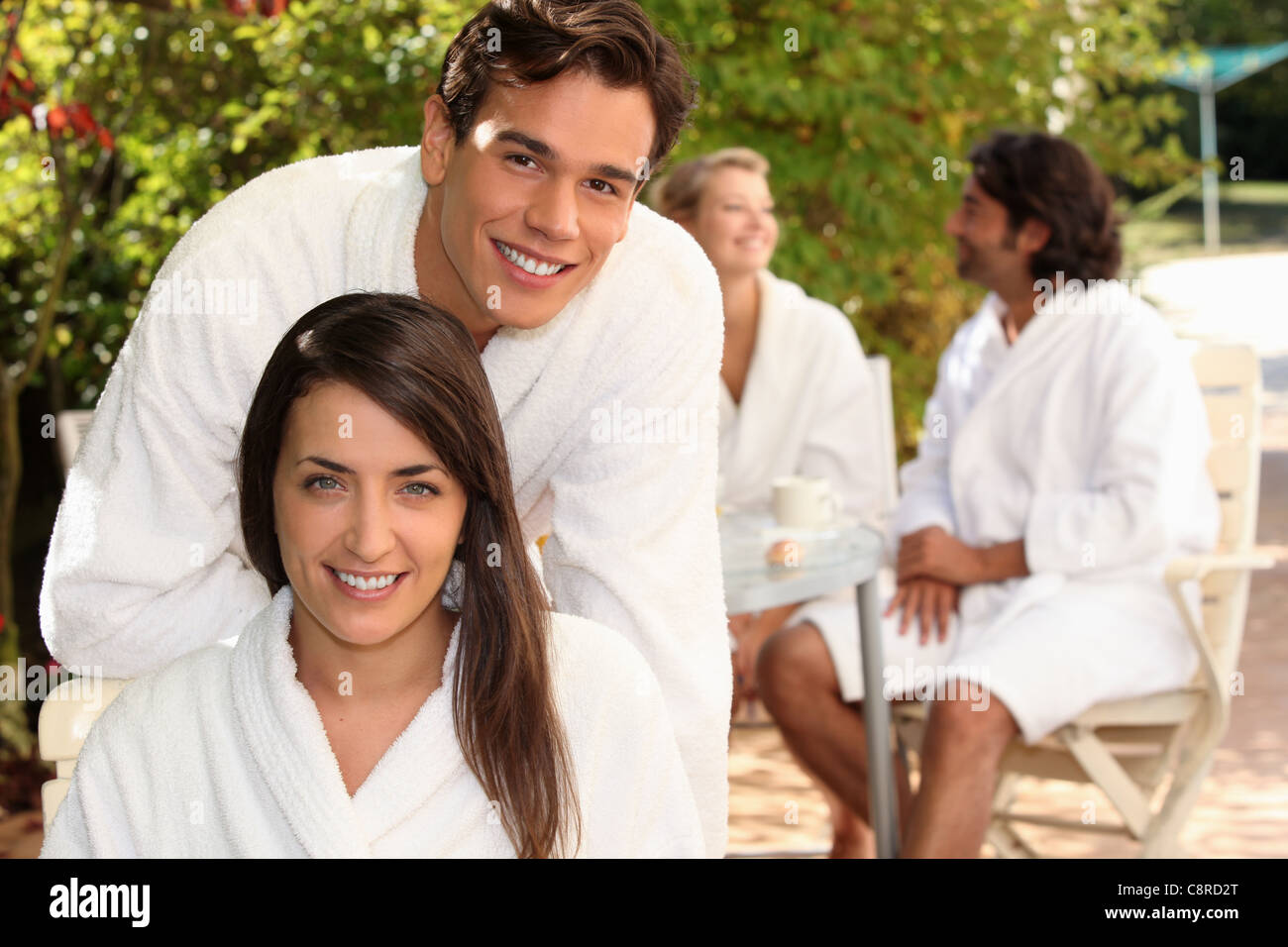 Young couple in bathrobes sitting on a terrace with friends Stock Photo