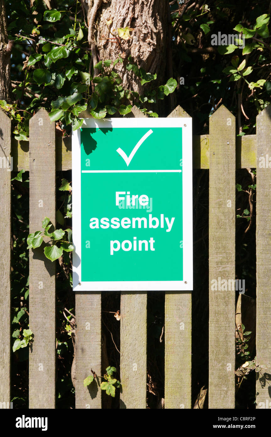 A sign on a wooden fence marks a Fire Assembly Point - Stock Image