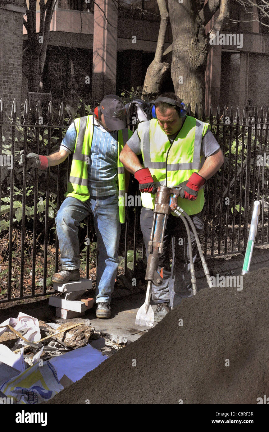 construction workers wearing safety headphones breaking up pavement to dig into sewage pipes Stock Photo