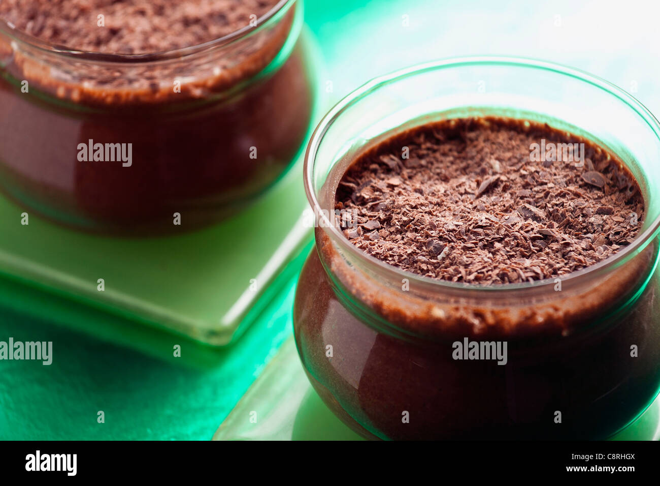 Close-up photograph of two chocolate mousse pots set on a green background - Stock Image
