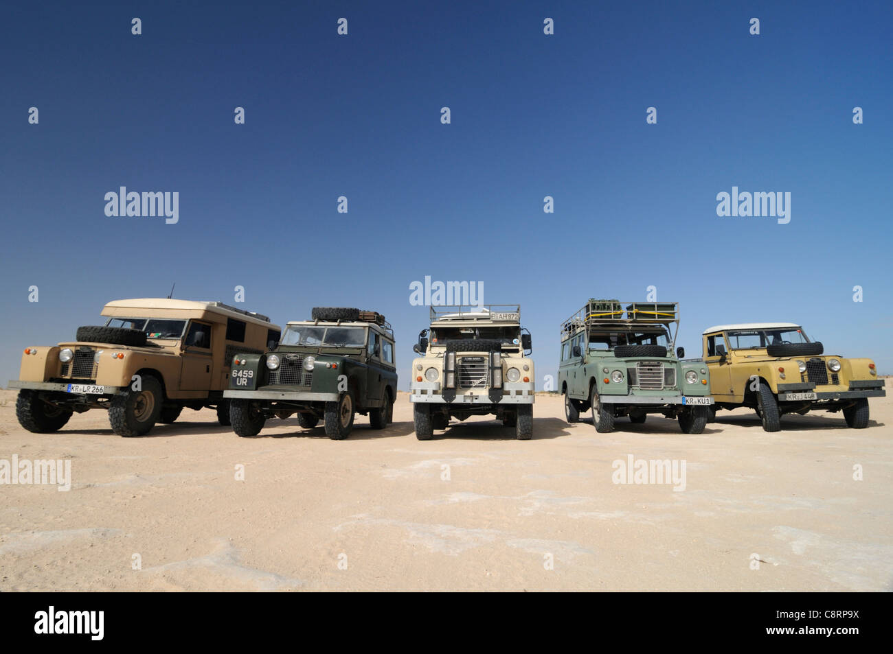 Africa, Tunisia, south of Douz. A group of five historic Series Land Rovers lined up for a journey through the desert - Stock Image
