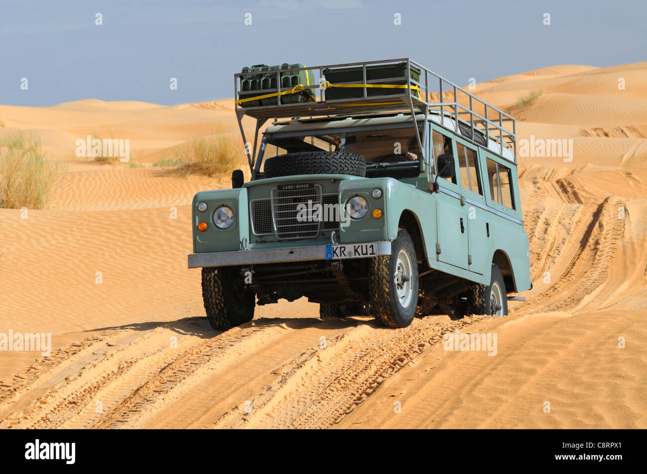 Africa, Tunisia, nr. Tembaine. Desert tourists driving their Land Rover Series 3 Station Wagon through a sandfield - Stock Image