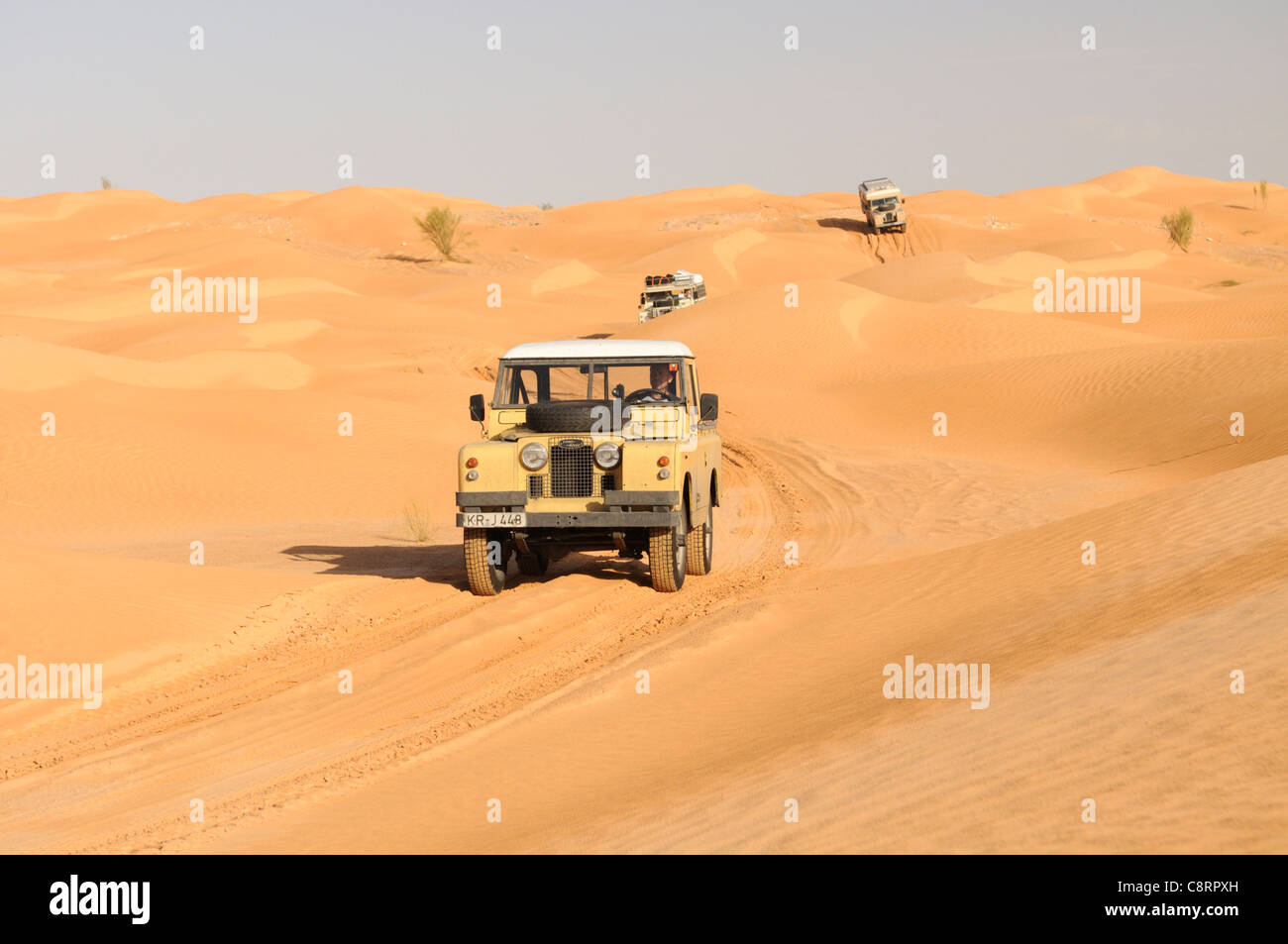 Africa, Tunisia, nr. Tembaine. Desert travellers with their historic Series Land Rovers crossing through a sandfield - Stock Image