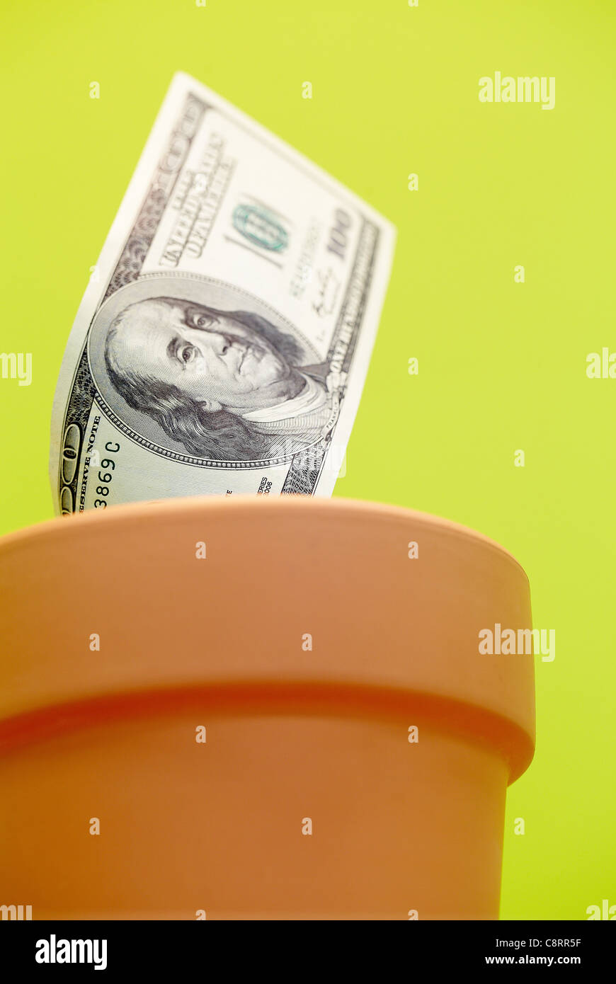 Close-up of one hundred dollar bill on flower pot - Stock Image