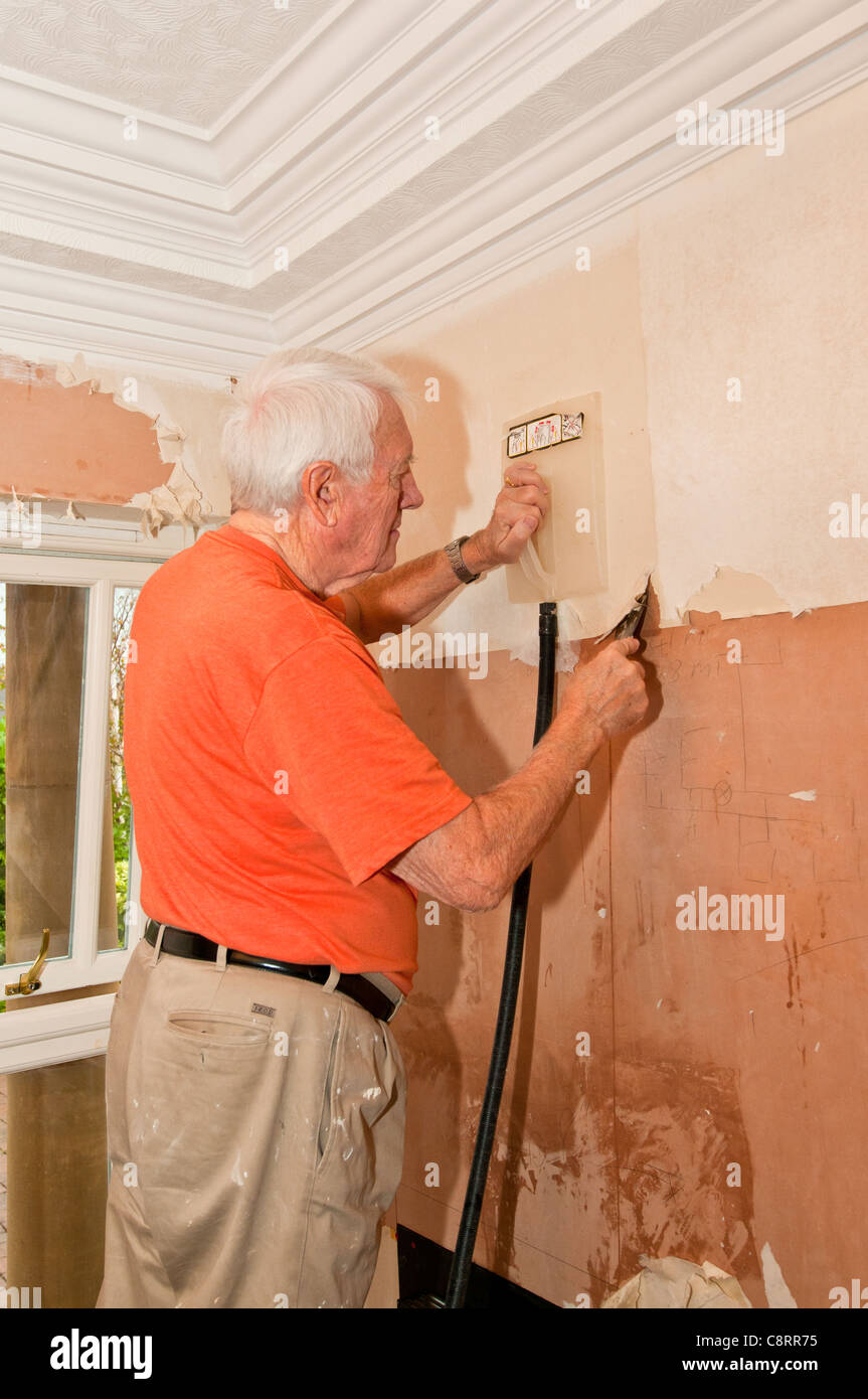 Man Stripping Wallpaper From Wall