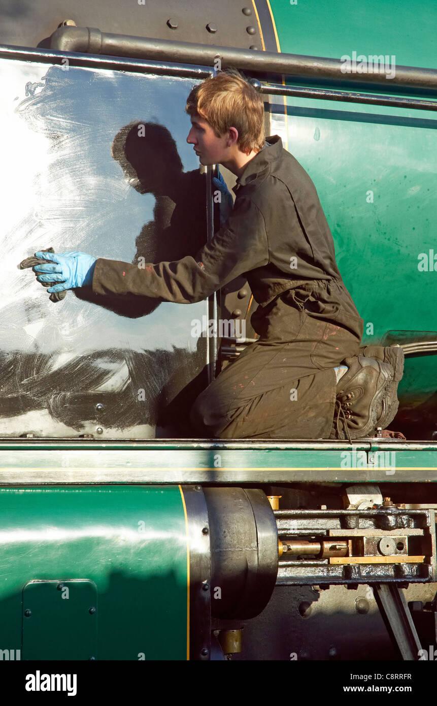 Mid-Hants Railway Autumn Gala 28/10/11. Young engine cleaner polishing the smoke deflectors on the express engine - Stock Image
