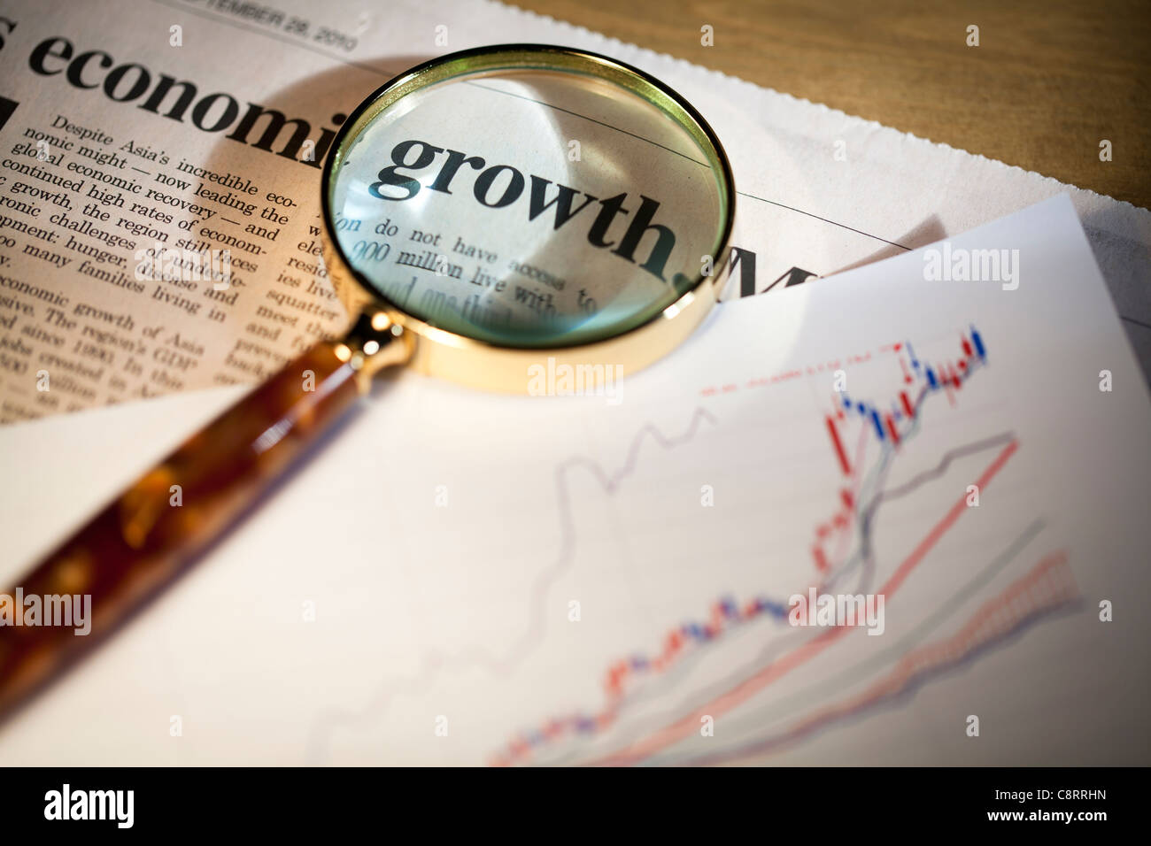 Close-up of headline of newspaper through magnifying glass and growth chart - Stock Image