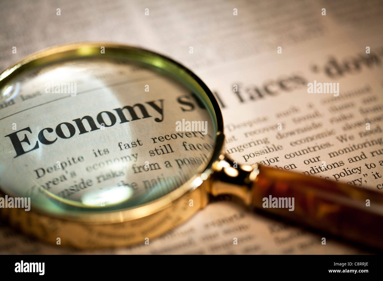 Looking at headline on financial page of newspaper through magnifying glass - Stock Image