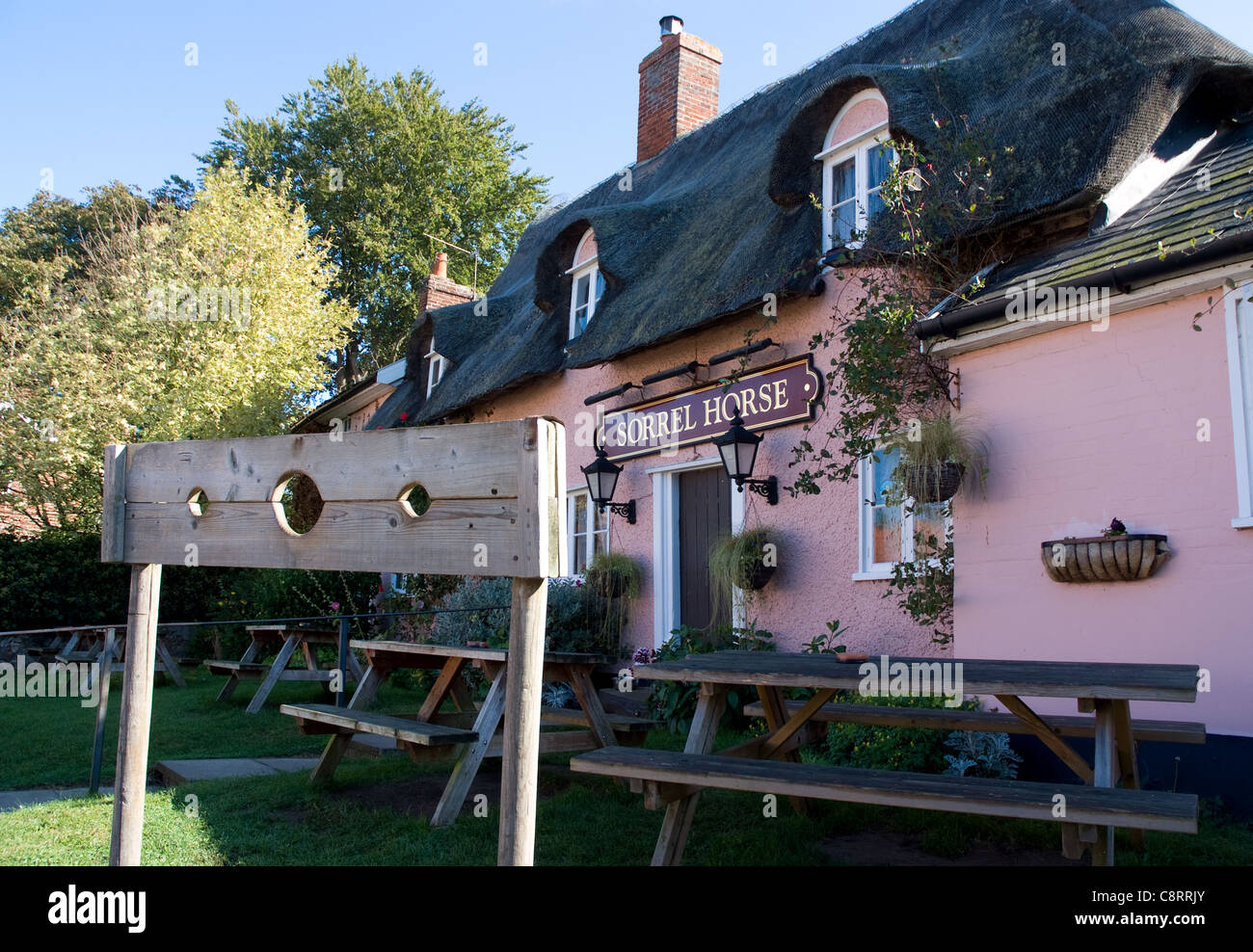 Medieval stocks outside The Sorrel Horse pub in Suffolk - Stock Image