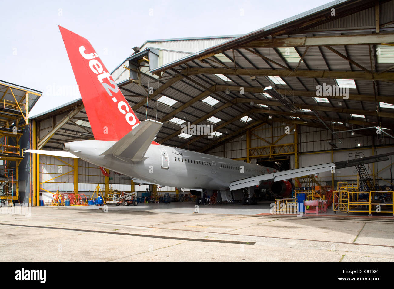 Boeing 757 in maintenance hangar with technicians in attendance - Stock Image