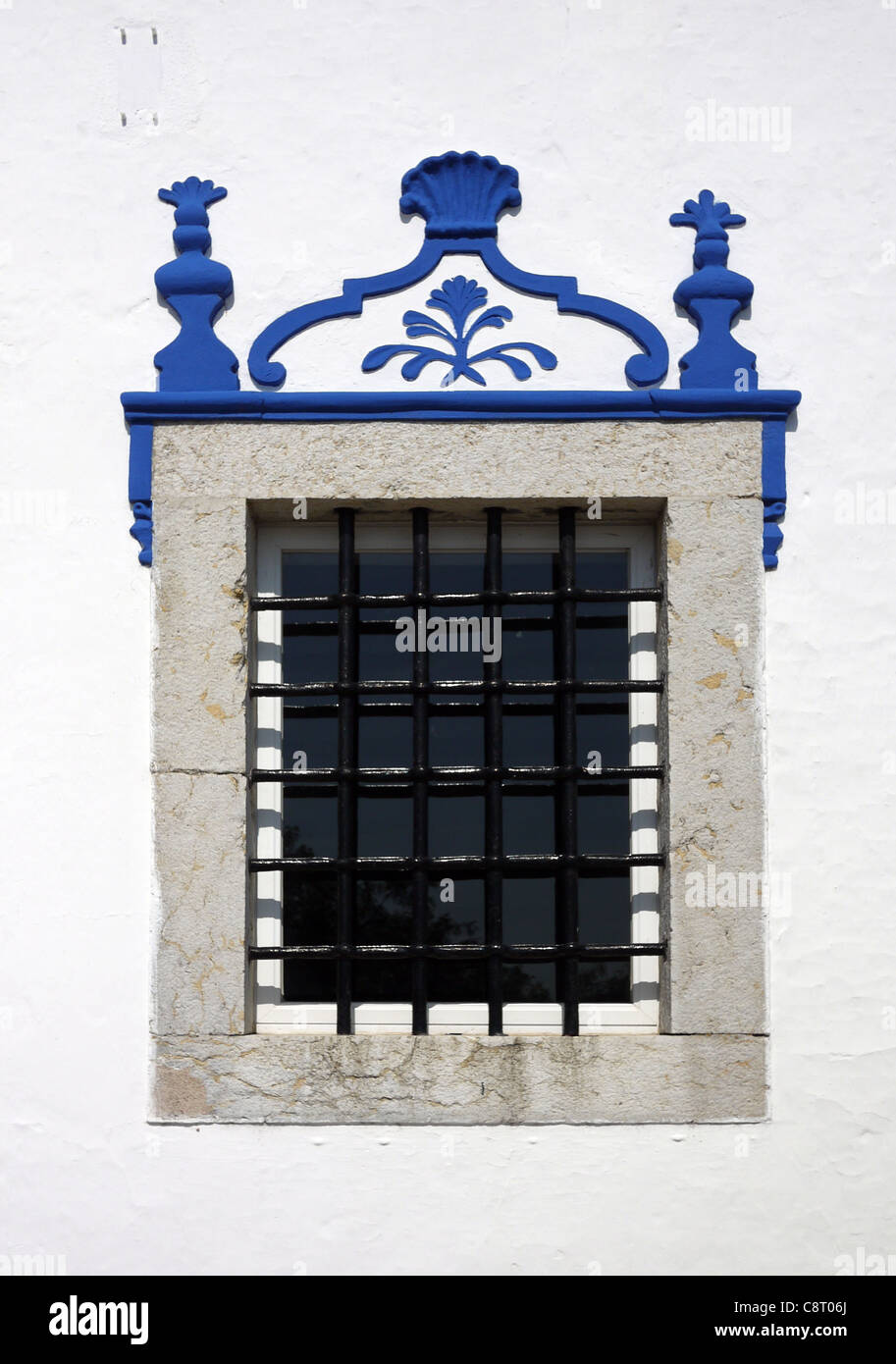 A barred window at the striking blue and white Church of Our Lady of the Castle, Coruche, Portugal. - Stock Image