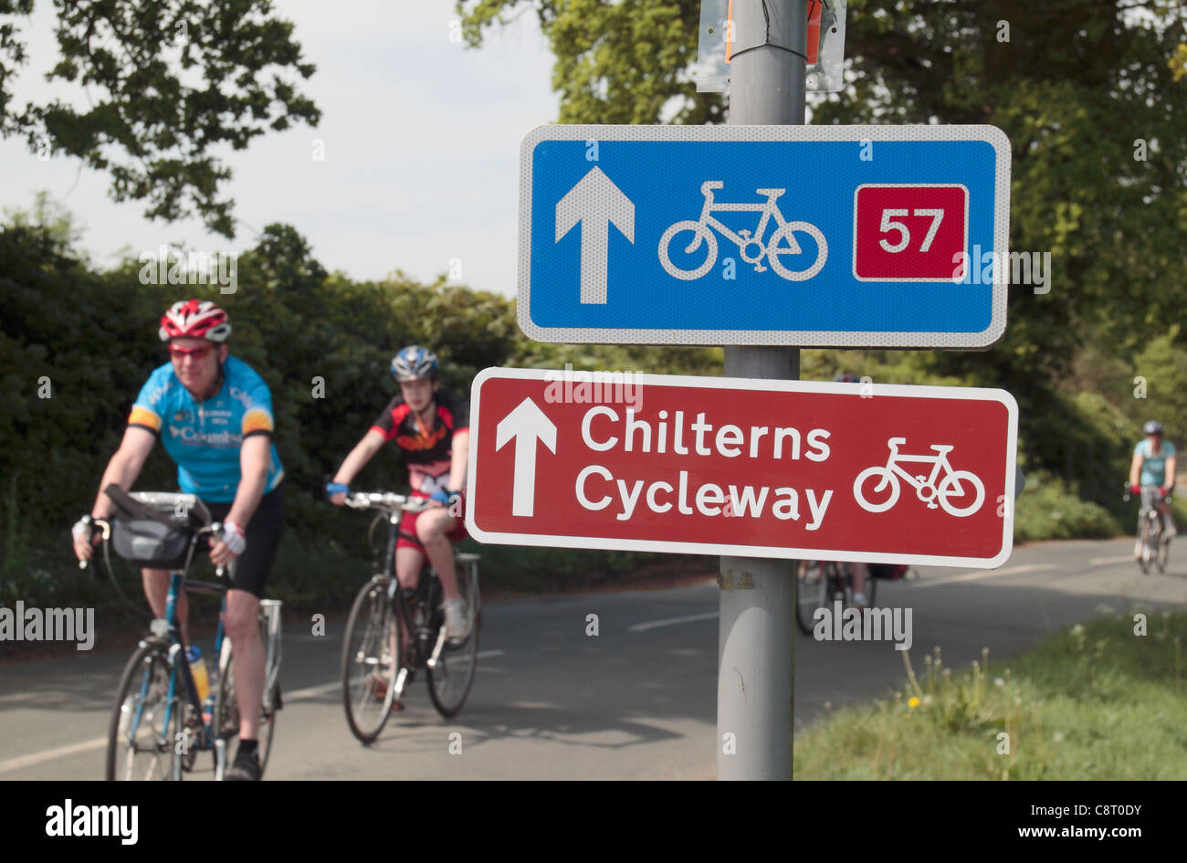 Cyclists ride past road signs for the Chilterns Cycleway and national cycle route 57 near Great Missenden, Buckinghamshire, - Stock Image