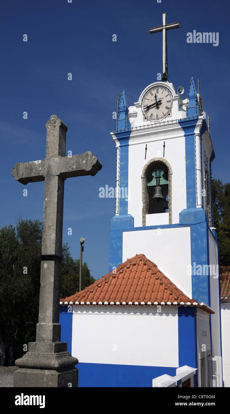 The cross and bell tower (clock tower) of the Church of Our Lady of the Castle, Coruche, Portugal. - Stock Image