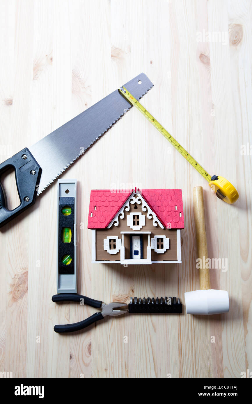 Top view of artificial model of house surrounded with tools - Stock Image