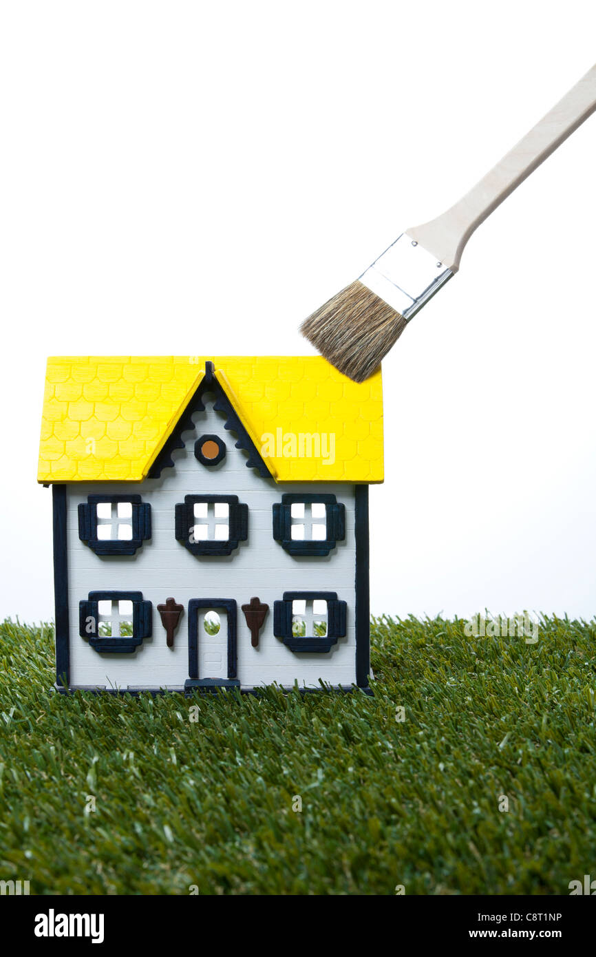 Model of house with paintbrush against white background - Stock Image