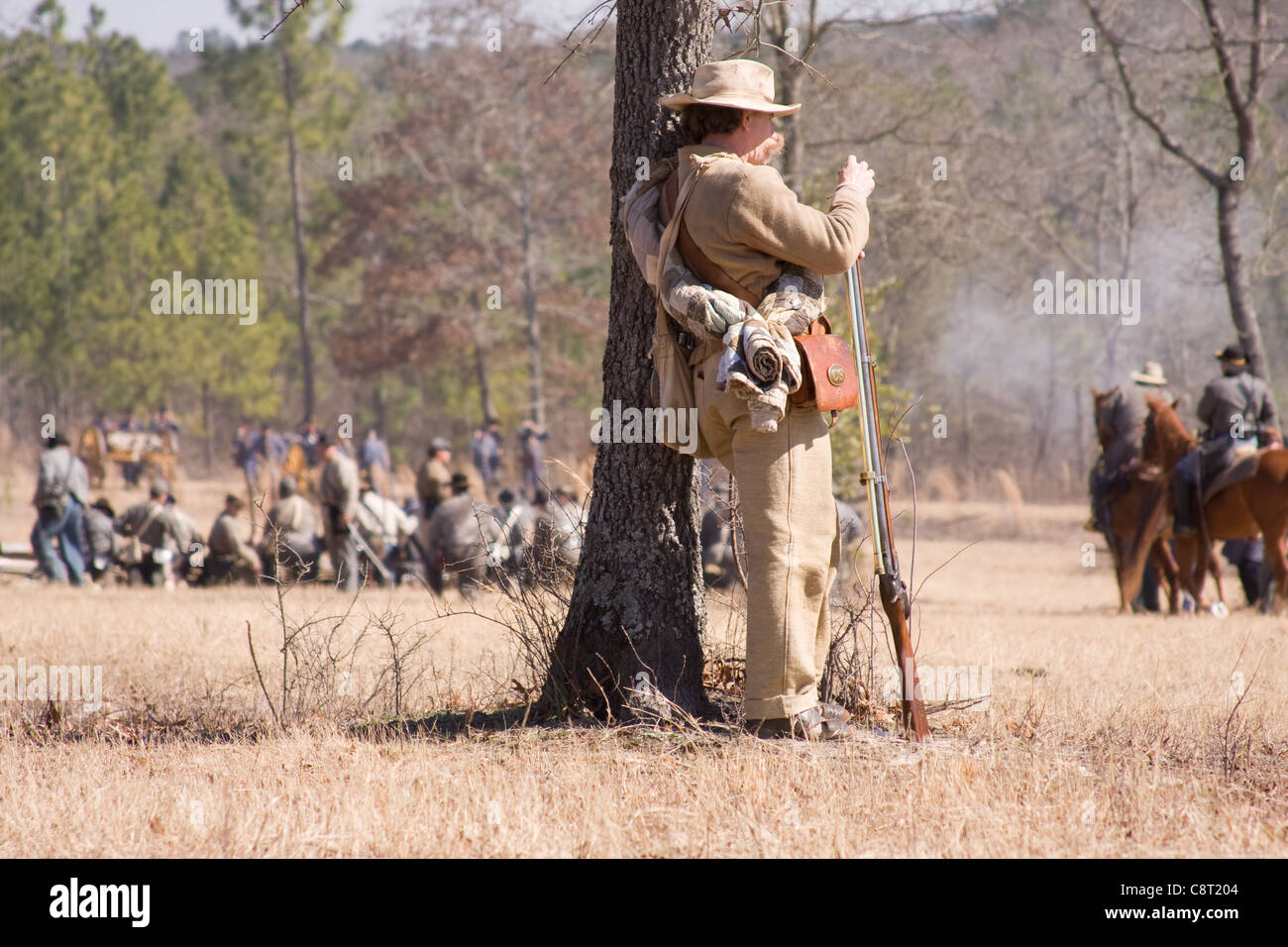 Revolutionary war scout watching the battle from behind a tree - Stock Image