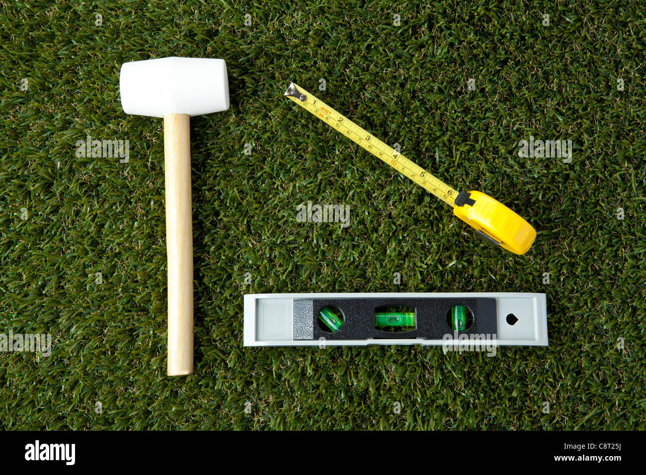 Top view of instruments of measurement with hammer on grass - Stock Image