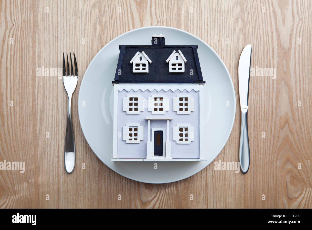Top view of model house placed in plate with fork and knife on table Stock Photo